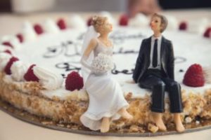 A cake featuring figurines of a husband and wife